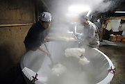 Brewery staff hands shovel out steaming rice to be cooled on a conveyor belt at the beginning of the brewing process of sake, a wine-like beverage fermented from rice, water, yeast and a starch-killing mold called koji-kin, at a sake brewery in Kyoto, Japan. More than 1,200 sake breweries exist in Japan, though falling domestic consumption has lead some to look to  overseas markets...Photographer: Robert Gilhooly