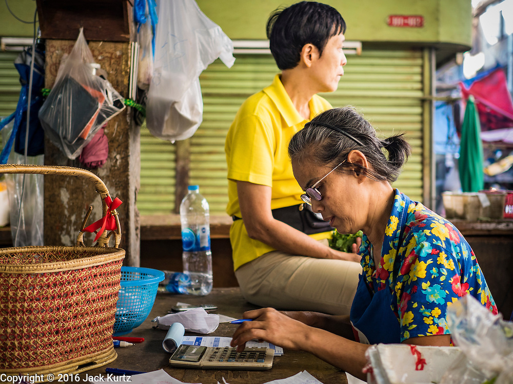 04 JANUARY 2016 - BANGKOK, THAILAND:        A shopkeeper in Bang Chak Market does her books before the market closed permanently Monday. The market closed January 4, 2016. The Bang Chak Market serves the community around Sois 91-97 on Sukhumvit Road in the Bangkok suburbs. About half of the market has been torn down. Bangkok city authorities put up notices in late November that the market would be closed by January 1, 2016 and redevelopment would start shortly after that. Market vendors said condominiums are being built on the land.     PHOTO BY JACK KURTZ