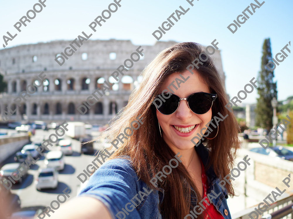 Happy young and smiling girl wearing sunglasses does a selfie with the colosseum in the background during the day