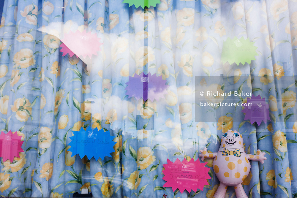 A Mr Blobby inflatable toy stands in the curtained and stickered window of an unconventional toy shop in East Dulwich.