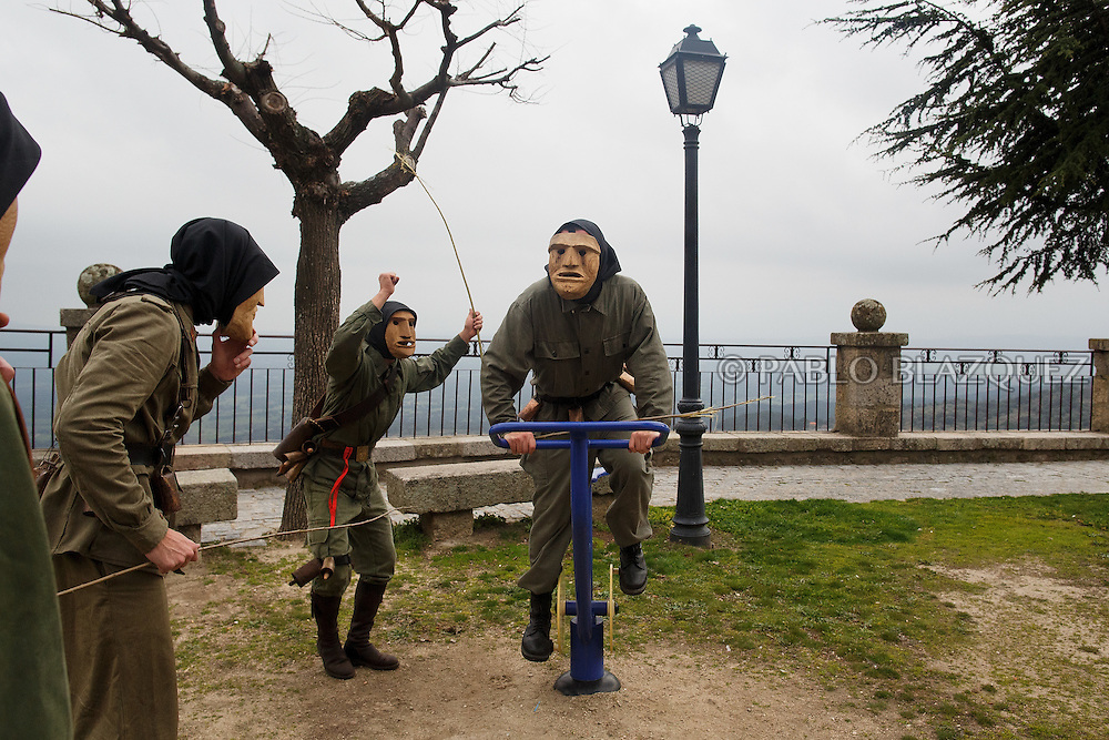 The Machurreros from Pedro Bernardo cheer another one using a stationary bicycle in a park during Carnival on February 6, 2016 in Pedro Bernardo, in Avila province, Spain. The origins of this pagan festival are unknown. The Machurreros wear wood masks, a military dress, black handkerchief, cowbells, and hold wicker stick. The festival disappeared after Dictator Franco forbid carnival festivals in 1937, but it was recently recovered. Before disappearing, male villagers after the military service, used to dress as Machurreros as they run along the streets scaring children and adults with their wicker stick to bring fertility to the land and expel the evil spirits. (© Pablo Blazquez)