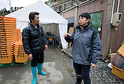 Takeshi Tachibana (R) and Hiromitsu Ito of Oh! Guts! stand next to the temporary fishing facilities in Ogatsu, Ishinomaki, Miyagi Prefecture, Japan on 01 Dec 2011. .Photographer: Robert Gilhooly