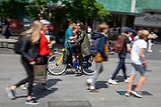 In Eindhoven fietst een vrouw op een OV-fiets tussen de voetgangers op het 18 septemberplein.<br /> <br /> In Eindhoven a woman cycles on a public transport bicycle between the pedestrians in the city center.