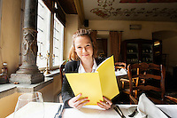 Smiling customer holding menu at restaurant table
