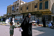 An Iraqi Shiite woman and her son carry groceries back from the market in Karbala, Iraq, Wednesday, July 23, 2003. Models of self-determination, Shiite controlled areas like Karbala are safer and starting to thrive more than under Saddam Hussein's regime. As the Shiite spiritual leader Ayottallah Ali Sistani has told his people to have patience with America, their patience is wearing thin with what they perceive as an occupation.