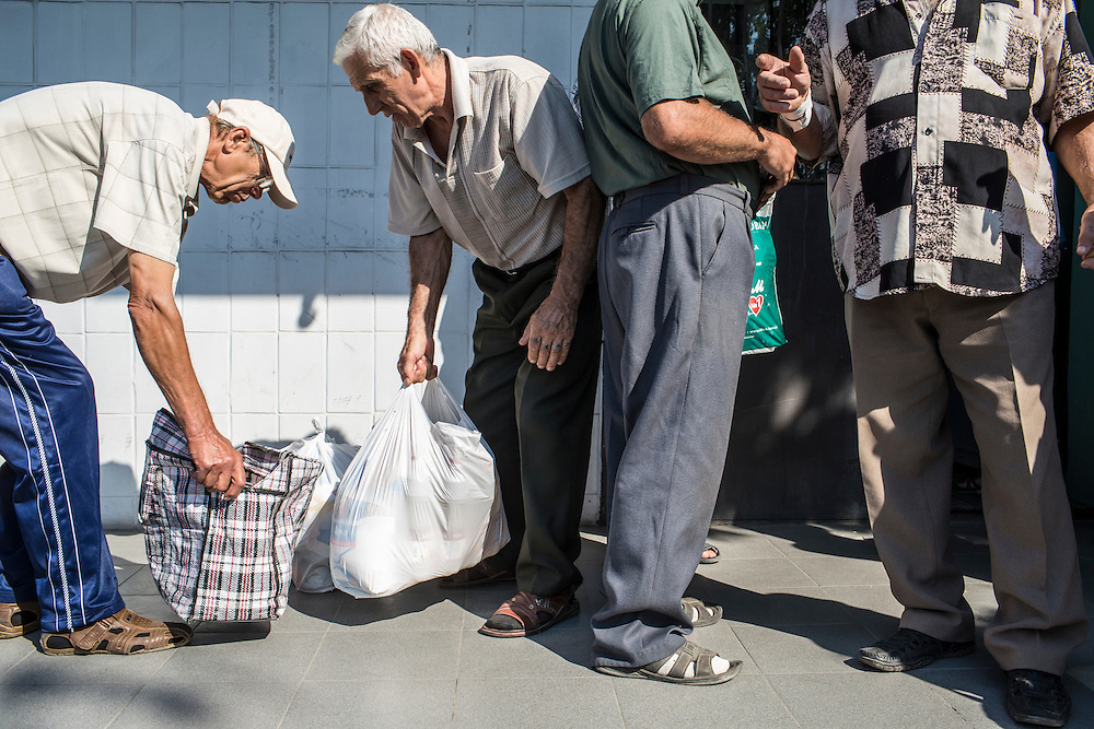 SARTANA, UKRAINE - AUGUST 29, 2015: Two men at left carry out bags of staple products such as flour during the distribution of humanitarian aid in Sartana, Ukraine. The village of Sartana, on the northeastern outskirts of Mariupol, has been relatively close to the front line between Ukrainian and pro-Russian rebel forces, with many incidents of shelling damaging homes and injuring or killing civilians. CREDIT: Brendan Hoffman for The New York Times