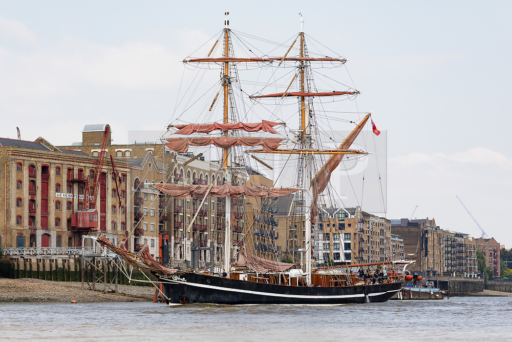 "© Licensed to London News Pictures. 23/05/2018. London, UK. The 107 year old tall ship, ""Eye of the Wind"" sails on the River Thames in front of historic wharves in Wapping during a London visit to join celebrations to mark forty years since the start of Operation Drake - a two year round the world expedition, of which Eye Of The Wind was the flagship. One of the last traditional sailing ships left, Eye of the Wind was originally built in Germany in 1911 as a Schooner but was given a new lease of life in 1973 when she was bought by Anthony ""Tiger"" Timbs, an Englishman from greater London. A group of enthusiastic ship lovers began to rig the vessel as a brigantine and her full restoration at a shipard in Faversham, Kent took nearly four years to complete. Photo credit: Vickie Flores/LNP"
