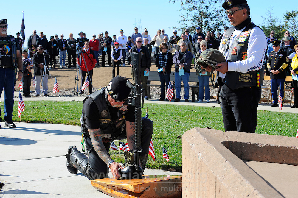 Gene Blakeman, kneeling, and Pete Quiane, right, from the American Legion Riders retire the Fallen Soldier at the Monterey County Vietnam Veterans Memorial. Color guards from the Salinas Police and Fire Departments and CIDU Monterey helped mark this solemn patriotic ceremony on Sunday in Salinas, held among hundreds of rippling flags at the memorial's hilltop location.