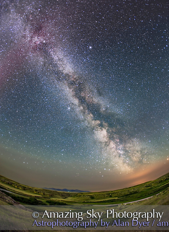 The summer Milky Way over the Milk River Valley and sandstone formations of Writing-on-Stone Provincial park, in southern Alberta. On the horizon are the volcanic Sweetgrass Hills in Montana. The red tint at top is from an aurora active that night and the ground is partly illuminated by green auroral light from the north. The Summer Triangle stars are at top left. Sagittarius is on the horizon sinking into the low clouds at botton right which are illuminated by lights from Sweetgrass, Montana. Clouds and smoke from forest fires to the west cut down the transparency and clarity of the sky this night, especially toward the horizon. <br /> <br /> This is a stack of 4 x 3-minute tracked exposures for the sky, and 4 x 5-minute untracked exposures for the ground, all with the 15mm Canon full-frame fish-eye and Canon 6D at ISO 1000, on the iOptron Sky-Tracker unit.
