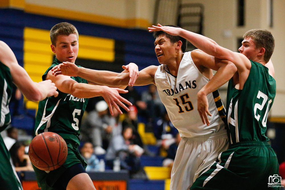 Milpitas guard Raymond Sangalang (15) is fouled by Palo Alto's defense during a layup attempt at Milpitas High School in Milpitas, California, on January 31, 2014.  Milpitas beat Palo Alto 51-39. (Stan Olszewski/SOSKIphoto)