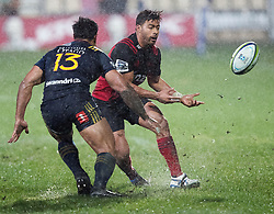 Crusaders Richie Mo'unga, right, offloads a pass as Highlanders Malakai Fekitoa lines up a tackle in the Super Rugby quarter final match, AMI Stadium, Christchurch, New Zealand, July 22 2017.  Credit:SNPA / Adam Binns ** NO ARCHIVING**