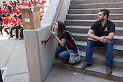 Monica Nezzer and Patrick Arite peak over the wall while waiting for an introduction to the group of prospective students to which they are to give a tour on Thursday June 2, 2016. Nezzer and Arite are both students at the University of New Mexico and are working 15-30 hours per week giving campus tours in order to help put themselves through college. (Steven St. John for NPR)
