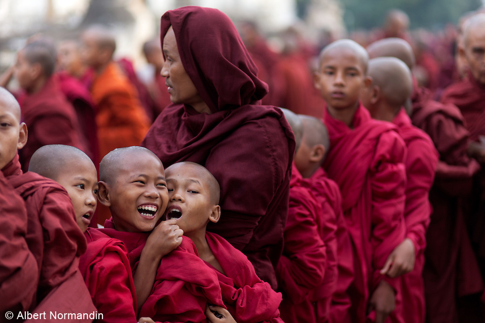 Young Monks fooling around in long line, Ananda Temple Festival, Bagan