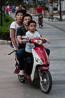 family riding moped in Shanghai China