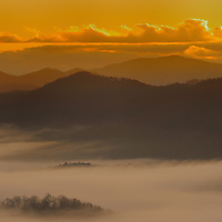 Sunrise in the Smoky Mountains photographed fron the Foothills Parkway with fog in the valley.