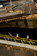 Workers walking over a floodgate at Miraflores Locks. Panama Canal, Panama City, Panama, Central America.
