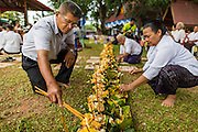 29 JUNE 2014 - DAN SAI, LOEI, THAILAND: People participate in a merit making ceremony on the last morning of the Ghost Festival at Wat Ponchai in Dan Sai. Phi Ta Khon (also spelled Pee Ta Khon) is the Ghost Festival. Over three days, the town's residents invite protection from Phra U-pakut, the spirit that lives in the Mun River, which runs through Dan Sai. People in the town and surrounding villages wear costumes made of patchwork and ornate masks and are thought be ghosts who were awoken from the dead when Vessantra Jataka (one of the Buddhas) came out of the forest. On the last day of the festival people participate in merit making ceremonies at the Wat Ponchai in Dan Sai and lead processions through town soliciting donations for the temple.    PHOTO BY JACK KURTZ