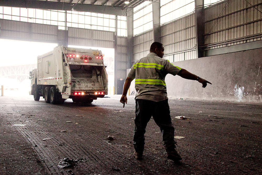 Back loader waste collection truck being guided into Transfer Station in Jersey City, NJ