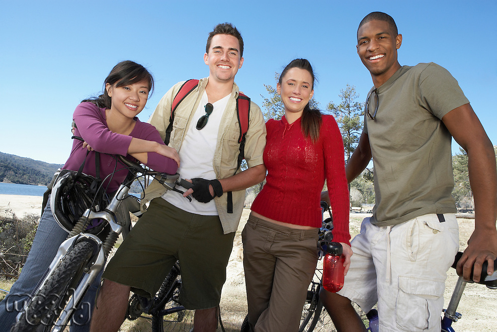 Four young adults standing on lake shore with mountain bikes.