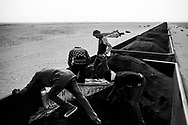 Zouarete, Mauritania - 24 January, 2016:<br /> Passengers prepare the wagon full of iron mineral for a long journey of 20 hours to Nouadhibou. Removing the iron that is on top to make less dust when the train is in motion.