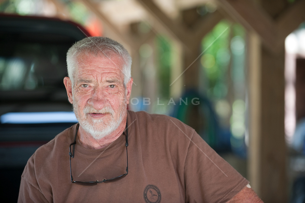 White haired elderly man sitting on the back of a truck