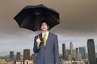 Business man holding umbrella in city