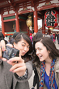 Young women sightseeing at Sensoji Temple, Asakusa, Tokyo.