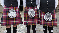 Detail of three men wearing tartan  kilts with sporrans.