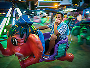 24 NOVEMBER 2015 - BANGKOK, THAILAND: A man rides an elephant merry go round at the Wat Saket temple fair. Wat Saket is on a man-made hill in the historic section of Bangkok. The temple has golden spire that is 260 feet high which was the highest point in Bangkok for more than 100 years. The temple construction began in the 1800s in the reign of King Rama III and was completed in the reign of King Rama IV. The annual temple fair is held on the 12th lunar month, for nine days around the November full moon. During the fair a red cloth (reminiscent of a monk's robe) is placed around the Golden Mount while the temple grounds hosts Thai traditional theatre, food stalls and traditional shows.       PHOTO BY JACK KURTZ