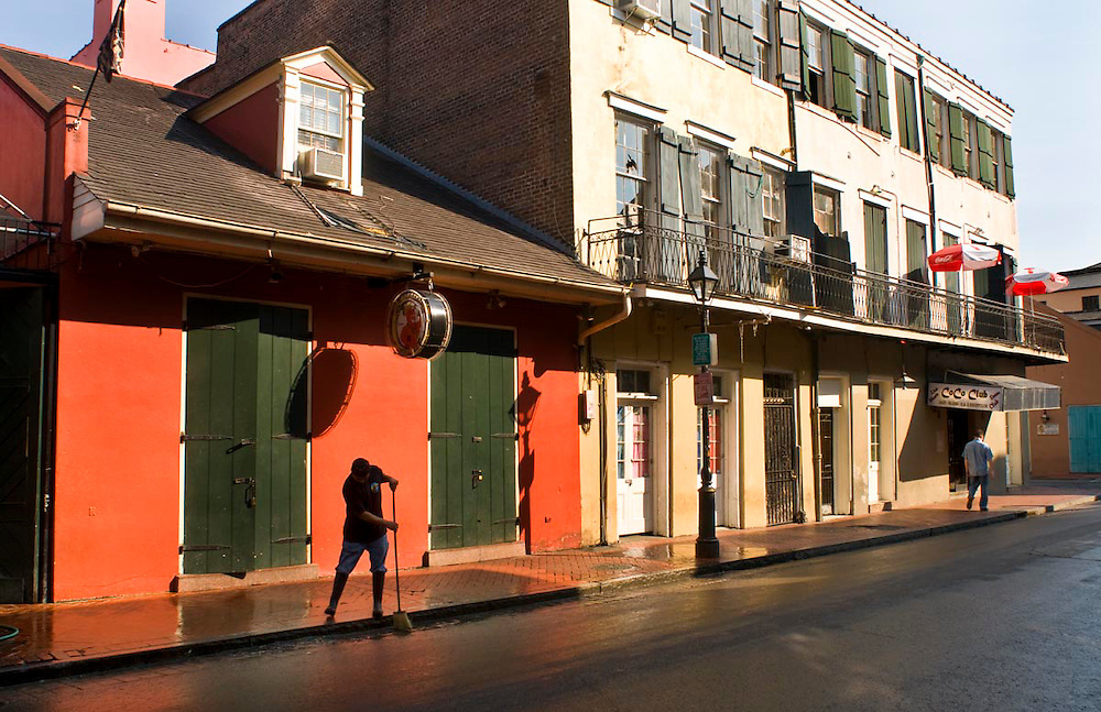 A local worker sweeps up any remaining litter before tourists and locals arrive. in front of CoCo nightclub on Bourbon St. in the French Quarter of New Orleans, LA.