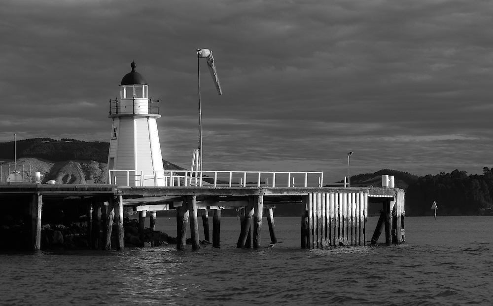 Late evening sunlight on the wooden lighthouse and windsock at the entrance to the port of Lyttelton, Canterbury, New Zealand