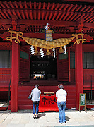 Iwaki shrine on the side of Mt. Iwaki which is a volcano and a very sacred mountain. In front ofthe main shrine building. People praying.