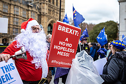 © Licensed to London News Pictures. 10/12/2018. London, UK. An anti-Brexit protester dressed as Father Christmas at a demonstration opposite Parliament. Photo credit: Rob Pinney/LNP