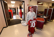 Equipment managers work in the Mal Moore Athletic Facility to get the University of Alabama football team ready for the trip to Baton Rouge to face LSU.  Thomas Hall holds AJ McCarron's back up jersey which he is preparing to pack as he talks with assistant equipment manager Larry Waters (not in photo).  Photo by Gary Cosby Jr.