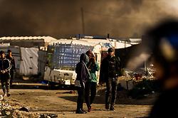 October 26, 2016 - Calais, France - Migrants leave the burning Calais Jungle, on October 26, 2016. Huge fires destroyed a mayor part of the refugee camp today. (Credit Image: © Markus Heine/NurPhoto via ZUMA Press)