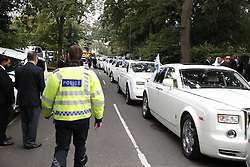 © Licensed to London News Pictures. 21/08/2018. Ashtead, UK. A policeman tries to control the traffic as a fleet of 16 Rolls Royce Phantom cars arrive at St Michaels Church in Ashstead for the funeral of traveller Mikey Connors. 32 year-old Mikey Connors, the nephew of My Big Fat Gypsy Wedding star Paddy Doherty, was killed when his horse-and-cart was hit by a car in Thamesmead on July 28. Photo credit: Peter Macdiarmid/LNP