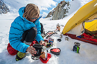 A female mountaineer as seen preparing food on a sunny day in the base camp on Col du Midi, at the foothills of Aiguille du Midi, Chamonix, France.