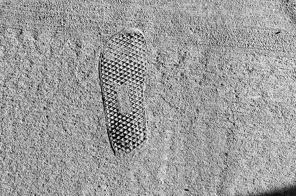 USA,Vereinigte Staaten von Amerika, Florida, Tallahasse. Ein Fußabdruck eines Schuhprofils bildet sich im Beton eines Weges ab  |  USA ,United States,United States of America, Florida,Tallahassee a foot print of a sole of a shoe fixed in the concrete of a side walk, pavement   |