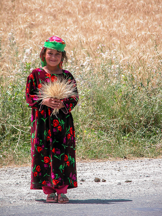 Portrait of a young Tajik girl with a posy of ripe wheat