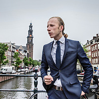 Nederland, Amsterdam, 2 juni 2016.<br /> <br /> Jelle Klaas, advocaat sociaal-economische mensenrechten.<br /> <br /> Jelle Klaas, lawyer at Fischer Advocaten, Social and Economic Human Rights Projectcoordinator Public Interest Litigation Project of NJCM.<br /> <br /> Op de foto: Jelle Klaas op de Prinsengracht met de Westeroren op de achtergrond.