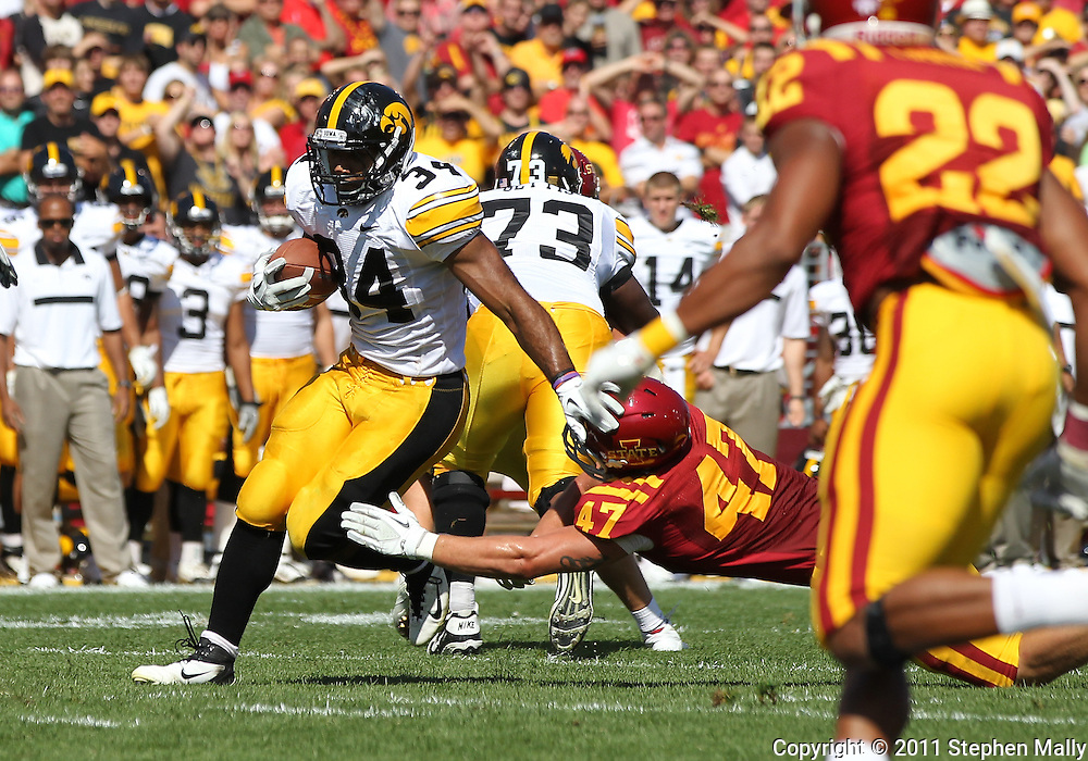 September 10, 2011: Iowa Hawkeyes running back Marcus Coker (34) tries to run out of a tackle by Iowa State Cyclones linebacker A.J. Klein (47) during the first half of the game between the Iowa Hawkeyes and the Iowa State Cyclones during the Iowa Corn Growers Cy-Hawk game at Jack Trice Stadium in Ames, Iowa on Saturday, September 10, 2011. Iowa State defeated Iowa 44-41 in 3OT.