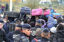 "A group of men with suitcases in a large queue of migrants outside a processing centre in ""the jungle"" near Calais, northern France, as the mass exodus from the migrant camp begins."