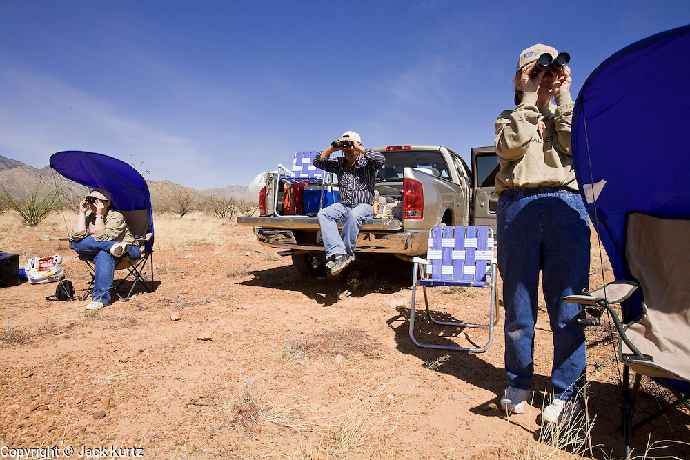 02 APRIL 2006 - THREE POINTS, AZ: VICKI DIETZ, left, from La Junta, CO, DAVE VYSTRCIL, center, from Tucson, AZ, and WANDA WEATHORFORD, from Denver, CO, all Minuteman volunteers scan the desert for signs of illegal immigrants during the Minuteman Project action on Elkhorn Ranch Rd. between Three Points, AZ, and Sasabe, AZ, about 60 miles south of Tucson, AZ, April, 2, 2006. Volunteers from the Minuteman Project have set up lines of observation posts on remote county roads in the desert southwest of Tucson to monitor the area for illegal immigrant traffic. On Saturday night, the first night of the action, Minuteman volunteers spotted more than 50 illegal immigrants and claim their tips to the US Border Patrol led to the apprehension of at least 16 of those immigrants.  Photo by Jack Kurtz