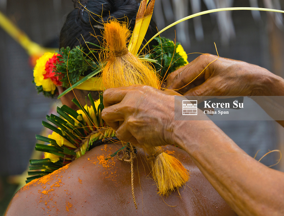 Yapese woman rubbing turmeric powder onto girl's skin to prepare forthe Yap Day Festival, Yap Island, Federated States of Micronesia