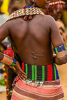 Hamer woman with scars on her back from ritual whipping, Hamer tribe weekly market in Turmi, Omo Valley, Ethiopia.