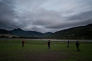 Arbi Khancoshvili play's football with his friends on the riverbank beside the village of Duisi, Republic of Georgia.