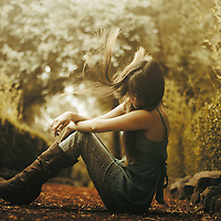 Portrait of a girl sitting in the ground outdoors edited with green hues.