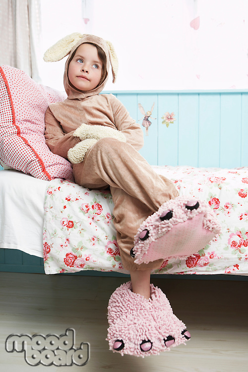 Young girl (5-6) sitting on bed wearing bunny costume and monster slippers