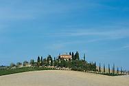 A stone farmhouse surrounded by cypress trees.  Tuscany, Italy