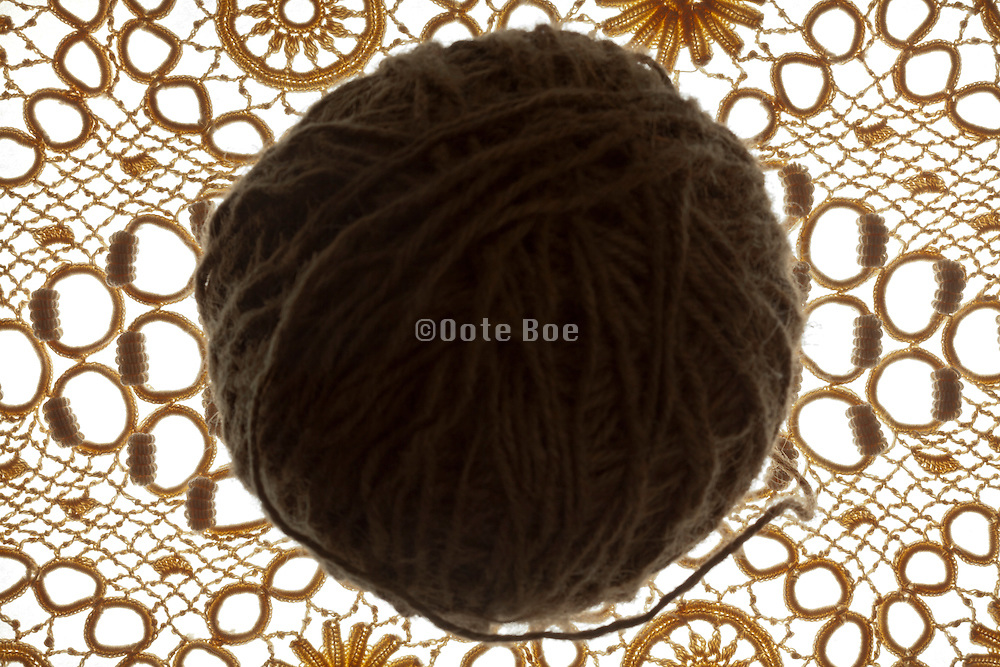lace fabric with ball of rough knitting yarn